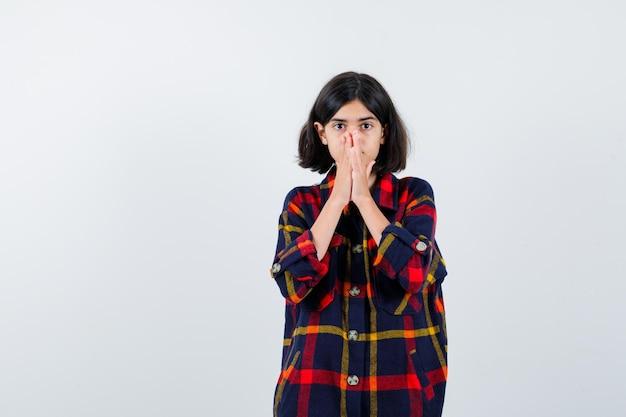 Молодая девушка закрыла рот и нос руками в клетчатой рубашке и выглядела удивленной. передний план.