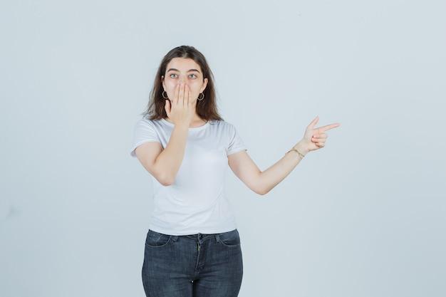 어린 소녀는 손바닥으로 입을 덮고, 티셔츠, 청바지 측면을 가리키고 충격을 받았습니다. 전면보기.