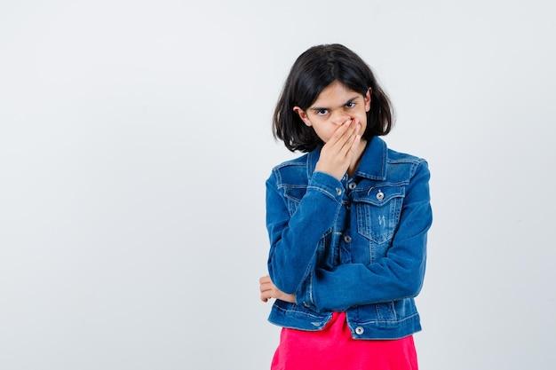 手で口を覆い、赤いtシャツとジージャンで拳を握りしめ、恥ずかしがり屋に見える少女、正面図。