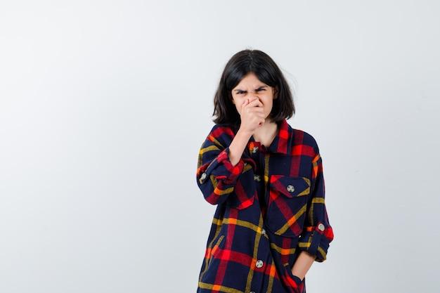 어린 소녀는 손으로 입을 가리고 체크 셔츠를 입고 찡그린 얼굴을 하고 해리를 찾고 있습니다. 전면보기.
