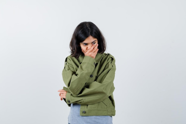 회색 스웨터, 카키색 재킷, 진 바지에 손으로 입을 가리고 피곤해 보이는 어린 소녀, 전면 보기.