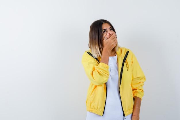 흰색 티셔츠, 노란색 재킷에 손으로 입을 덮고 쾌활한, 전면보기를 찾고 어린 소녀.