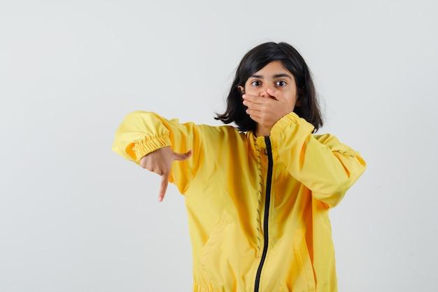 Giovane ragazza che copre la bocca con la mano, rivolto verso il basso con il dito indice in bomber giallo e guardando sorpreso.