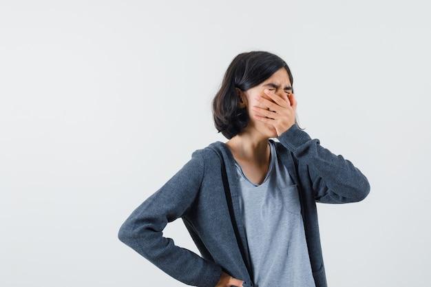 어린 소녀는 손으로 입을 덮고, 밝은 회색 티셔츠와 짙은 회색 지퍼 앞 까마귀로 하품하고 졸린 표정으로 허리에 다른 손을 얹습니다.