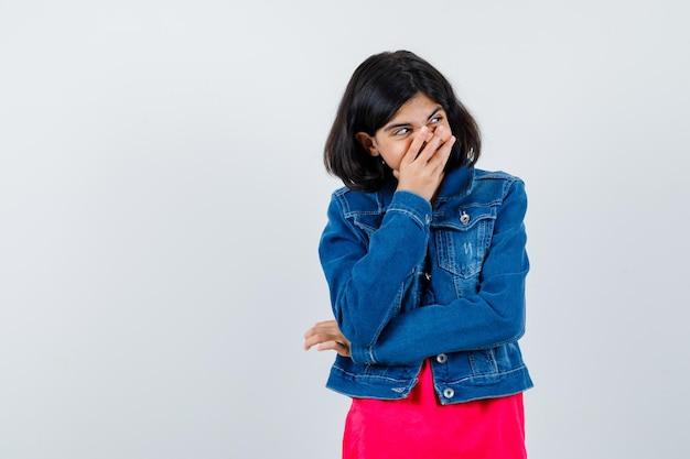 Ragazza che copre la bocca con la mano in maglietta rossa e giacca di jeans e sembra carina. vista frontale.