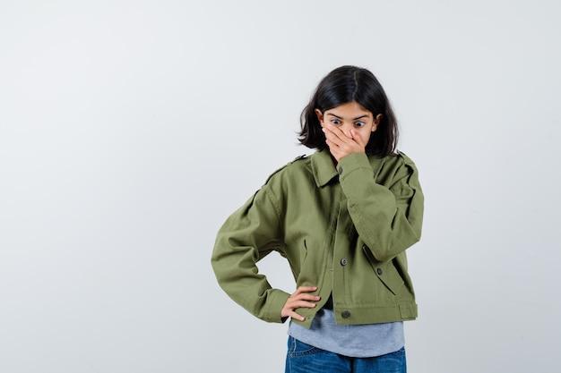 회색 스웨터, 카키색 재킷, 진 바지를 입고 허리에 손을 잡고 놀란 표정으로 입을 가리고 있는 어린 소녀. 전면보기.