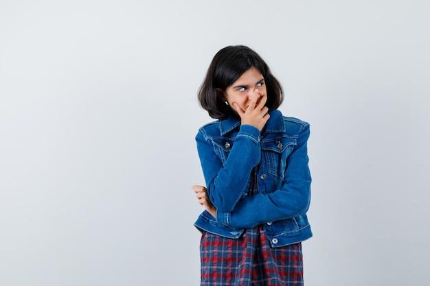 체크 셔츠와 진 재킷을 입고 웃으면서 귀엽게 보이면서 손으로 입을 가리고 있는 어린 소녀.