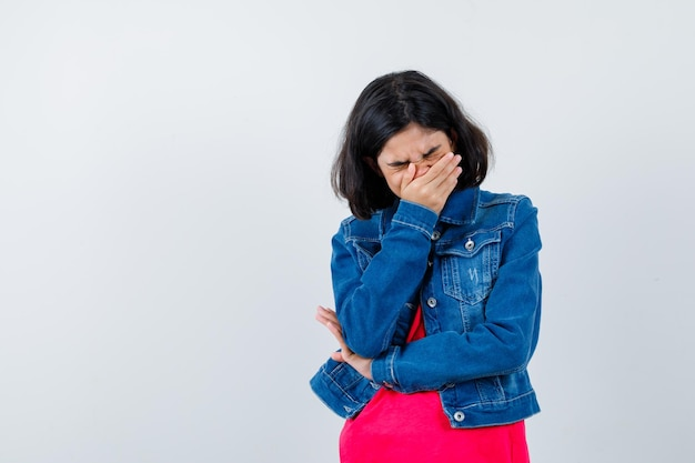 Ragazza che copre la bocca con la mano, sbadigliando in maglietta rossa e giacca di jeans e sembra stanca