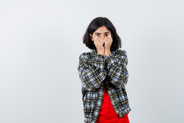 Young girl covering mouth with hands, clenching fists in checked shirt and red t-shirt and looking scared , front view.