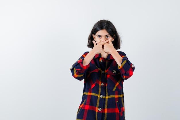 어린 소녀는 손으로 입을 가리고 체크 셔츠를 입고 다른 방향을 가리키고 진지한 정면을 바라보고 있습니다.