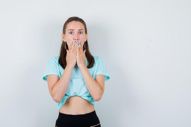 Giovane ragazza che copre la bocca con le palme in maglietta turchese, pantaloni e sembra spaventata, vista frontale.