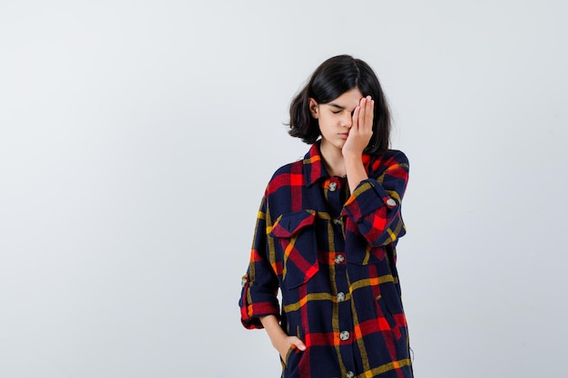 Young girl covering one eye while holding hand in pocket in checked shirt and looking tired. front view.