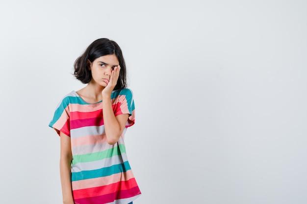 カラフルなストライプのtシャツで顔の一部を手で覆い、疲れ果てているように見える少女。正面図。