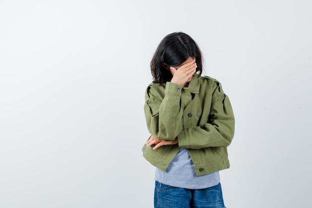灰色のセーター、カーキ色のジャケット、ジーンズのパンツで顔の一部を手で覆い、疲れているように見える少女、正面図。
