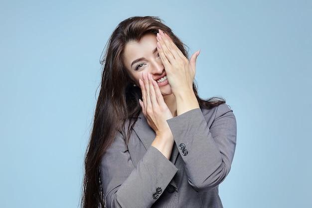 若い女の子は彼女の手で彼女の顔を覆います