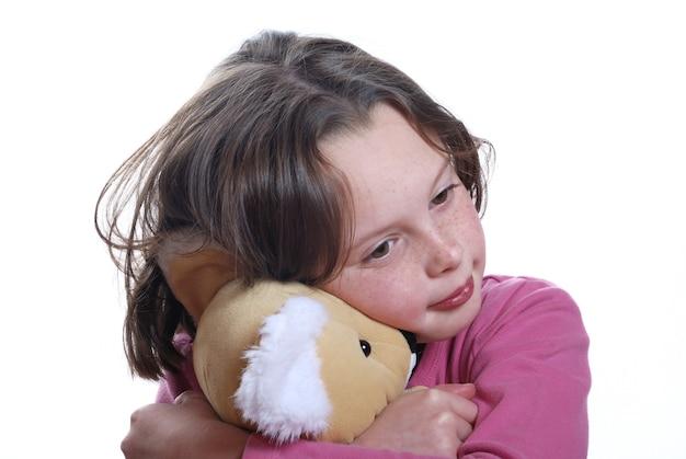 Молодая девушка обнимает плюшевого мишку