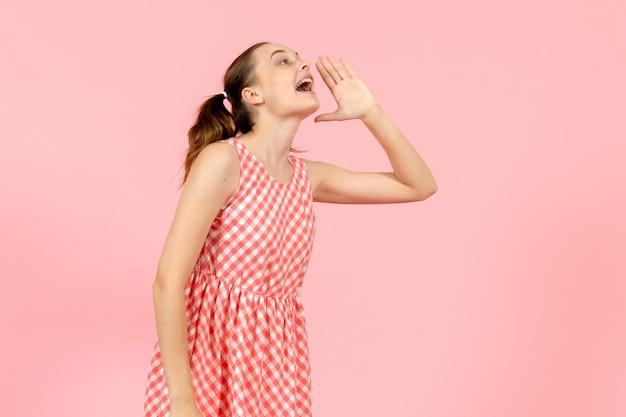 Giovane ragazza in abito luminoso carino chiamando ad alta voce qualcuno in rosa