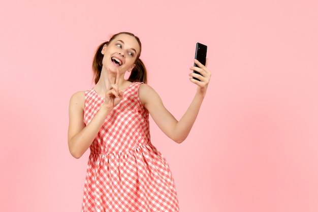 Young girl in cute bright dress taking selfie on pink