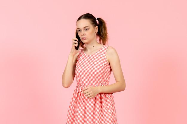 Giovane ragazza in abito luminoso carino parlando al telefono in rosa