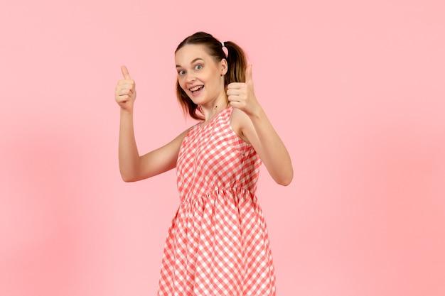 Giovane ragazza in abito luminoso carino con espressione eccitata sul rosa