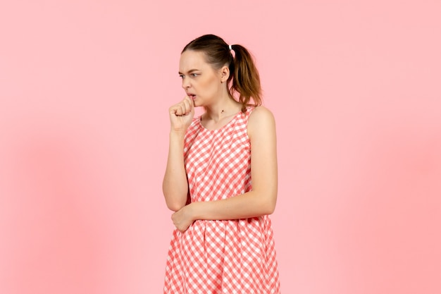 Young girl in cute bright dress with nervous expression on pink