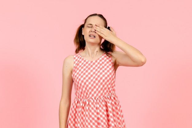 Young girl in cute pink dress crying on pink