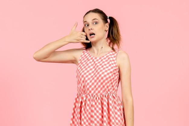 Giovane ragazza in carino abito rosa che mostra la telefonata posa sul rosa