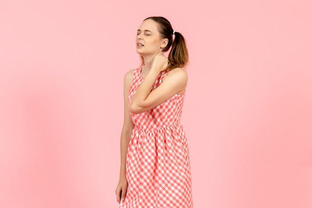 Giovane ragazza in abito rosa carino soffre di dolore al collo in rosa