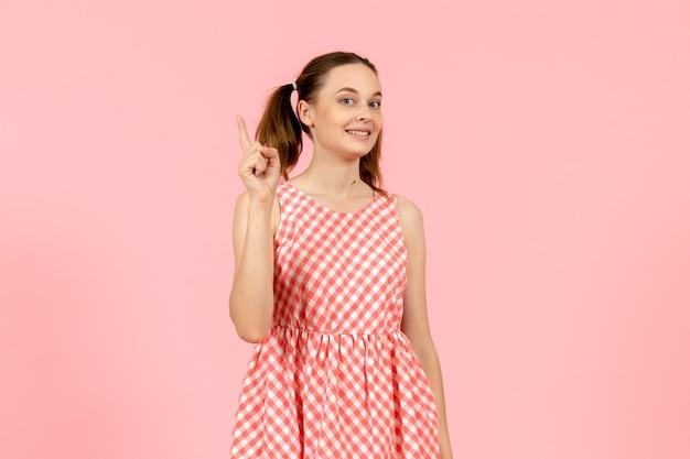 Giovane ragazza in abito rosa carino con espressione eccitata sul viso in rosa