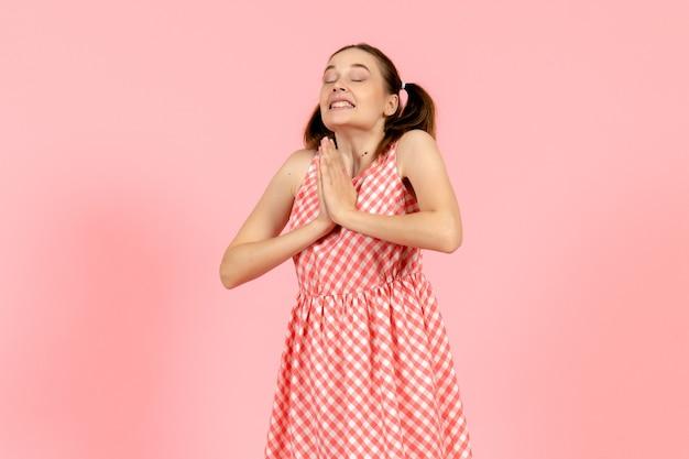 Giovane ragazza in abito rosa carino con espressione eccitata sul rosa