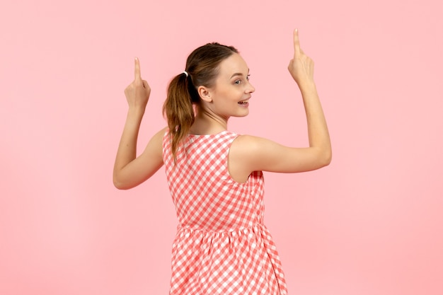 Giovane ragazza in abito rosa carino con expressionnd eccitato tornò sul rosa