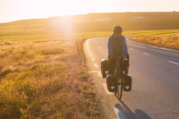 日没時にアイスランドサイクリストの舗装道路をサイクリングする少女
