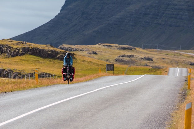 Young girl cycling on a paved road in iceland.