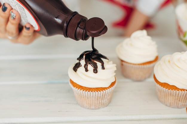 A young girl decorates cupcakes by pouring chocolate cream