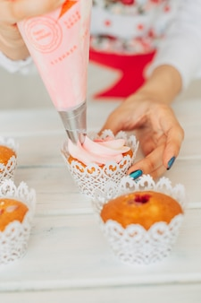 A young girl decorates cupcakes with cream.