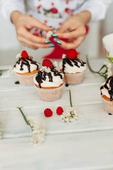 A young girl decorates cupcakes with fresh berries and flowers