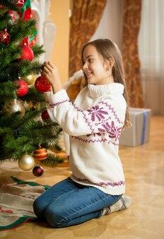 家でクリスマスツリーを飾る少女