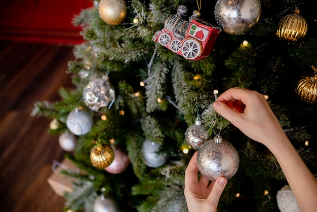 Young girl  decorating the christmas tree, holding some christmas baubles in her hand. horizontal view several objects copyspace holiday concept