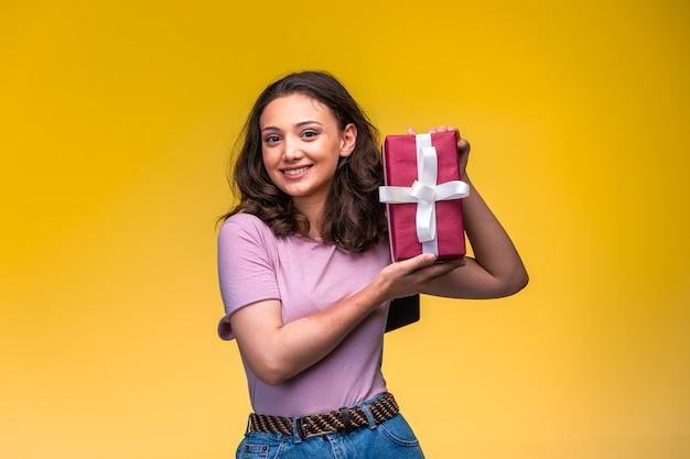 Молодая девушка демонстрирует свою подарочную коробку на желтой стене.