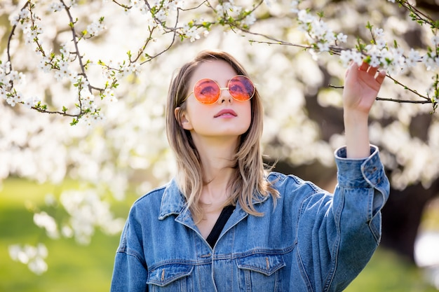 Young girl in a denim jacket and sunglasses stands near a flowering tree