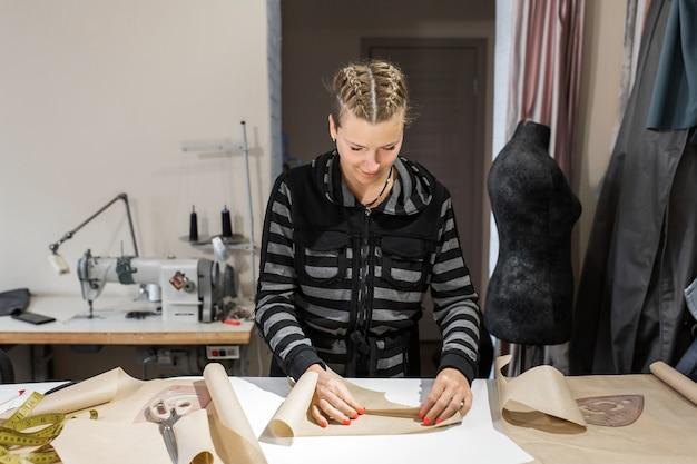 Молодая девушка дизайнер одежды сложенный бумажный узор. изготовление одежды на заказ концепт модельера