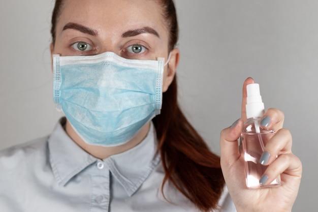 마스크에 어린 소녀 의사는 회색 배경에 그의 손에 소독제 스프레이를 보유하고