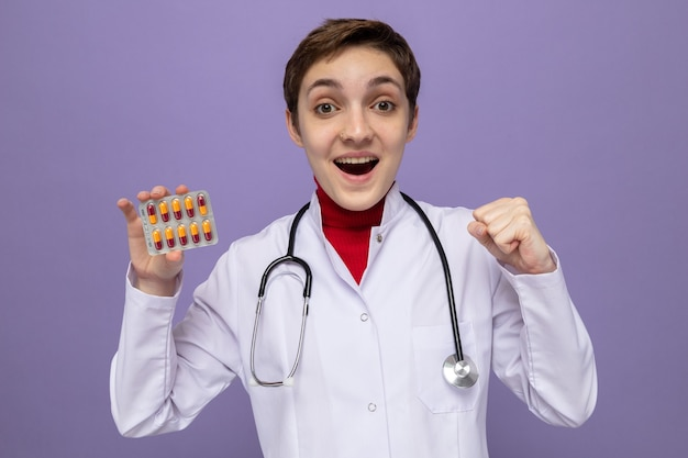 紫色の壁の上に立っている幸せで興奮した握りこぶしでブリスターを保持している首の周りに聴診器と白いコートの若い女の子の医者