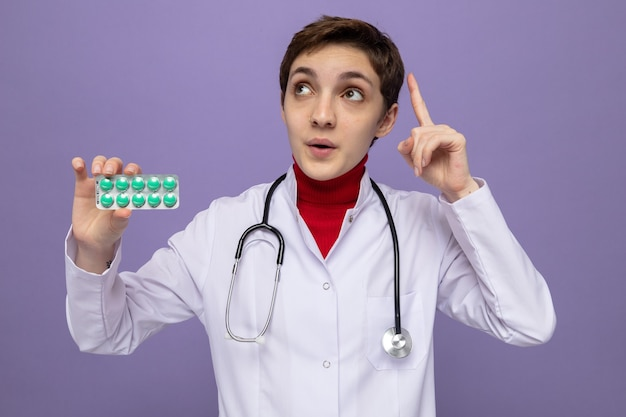 Молодая девушка-врач в белом халате со стетоскопом на шее держит блистер с таблетками, удивленно глядя вверх, показывая указательный палец, стоящий на фиолетовом