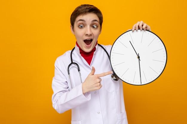 聴診器を持った白いコートを着た若い女の子の医者が人差し指で時計を指さし、目を細めて変な顔をして幸せで驚き、オレンジ色に立っている