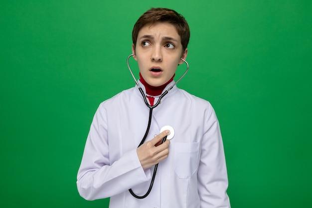 Молодая девушка-врач в белом халате со стетоскопом, прислушиваясь к ее сердцебиению, выглядит взволнованной, стоя на зеленом