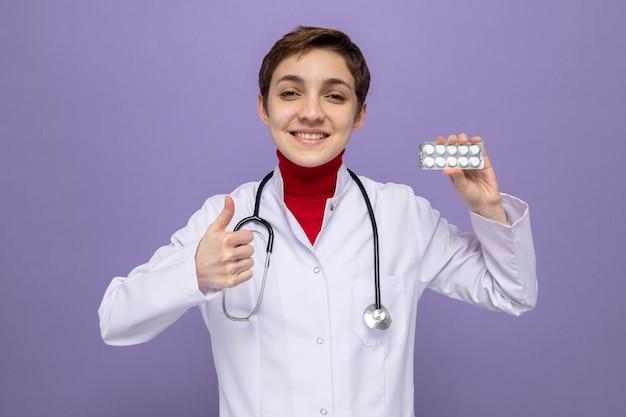 Medico della ragazza in camice bianco con lo stetoscopio intorno al collo che tiene la vescica con le pillole che sorride allegramente mostrando i pollici in su in piedi sul viola