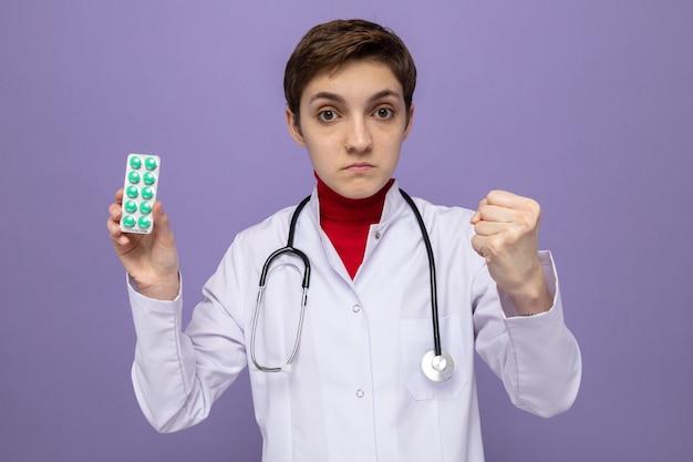 Medico della ragazza in camice bianco con lo stetoscopio intorno al collo che tiene la vescica con le pillole con la faccia seria che mostra il pugno che sta sopra la parete viola
