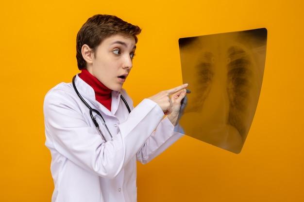 Giovane dottoressa in camice bianco con stetoscopio che tiene i raggi x dei polmoni guardandolo confuso in piedi sull'arancione
