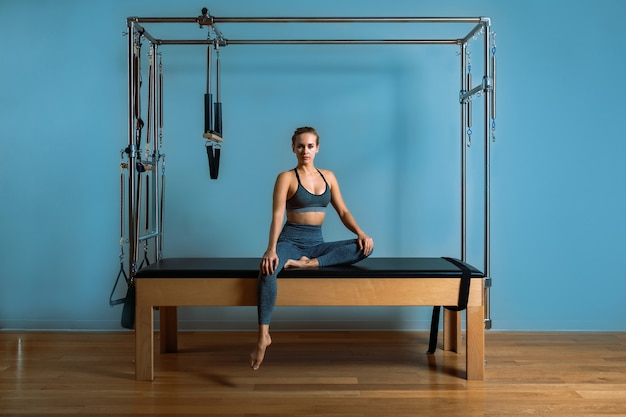 A young girl does pilates exercises with a bed reformer
